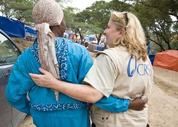 Liz O'Neill, asociada de comunicaciones de CRS, saluda a una mujer displazada en el campamento de Petitionville en Puerto Príncipe, donde CRS proporcionó alimentos y refugio a más de 40,000 residentes. Foto de David Snyder para CRS