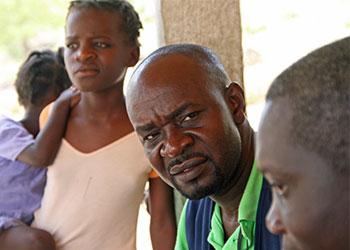 Enock Vilma, coordinador de Catholic Relief Services para el proyecto de localización y reunificación familiar en Haití, visita niños en un orfanato en las afueras de Gonaives. Foto por Lane Hartill/CRS