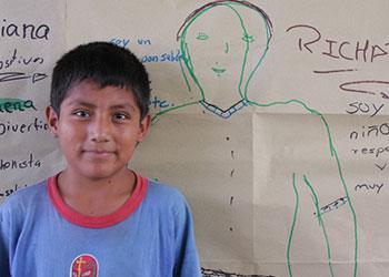 Richar Julca Daza, de 11 años, en frente del autorretrato que dibujó en el taller sobre autoestima. La sesión fue parte del programa del COCID para niños trabajadores en Soritor. Foto de Jim Stipe/CRS