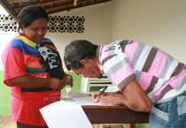 Brigida Rocha, una trabajadora social en el Centro para la Defensa de la Vida y los Derechos Humanos de Açailândia en Brasil, financiado por CRS, mira mientras Manuel Alves da Costa firma unos papeles para recibir el pago de su ex empleador, quien fue declarado culpable de practicar trabajo esclavo. Foto por Robyn Fieser/CRS