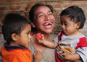 Lety Francisca Ramírez, de 22 años y con VIH, sostiene a sus hijos en su hogar en Guatemala. Los promotores de Gente Unida, socios de CRS, visitan los hogares de otros pacientes con VIH como Lety, para responder sus preguntas, examinar su estado de salud, distribuir alimentos y asegurarse que toman regularmente las drogas anti-retrovirales. Foto de Sara A. Fajardo/CRS