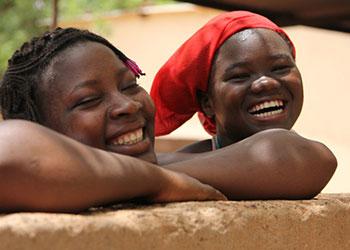 Dos jóvenes residentes del Centro para niñas vulnerables en Kaya, Burkina Faso de Catholic Relief Services observan como se prepara la comida en el patio del hogar. El centro ofrece un refugio seguro para las jovencitas que huyen de matrimonios forzados con hombres mucho mayores. Rechazadas por sus familias, ellas a veces caminan por largas horas para llegar al centro, donde aprenden a coser, cocinar y tejer. Lo más importante es que aprendan a cuidarse a sí mismas y a planear su propio futuro. Foto por Gina Kane/CRS.