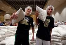 David Shafer (izquierda) y Michael Giebel (derecha) del equipo de soccer de la preparatoria católica Bishop Moore High School alzan 50 sacos de arroz. Foto por Jim Stipe/CRS