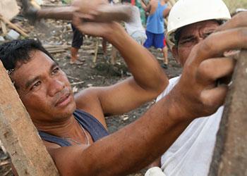 """Hermógenes """"John"""" Cortés, Jr. (izquierda) y un carpintero, dos asistentes, y varios voluntarios trabajan juntos para construir un refugio de emergencia para John y su familia. Jim Stipe/CRS"""