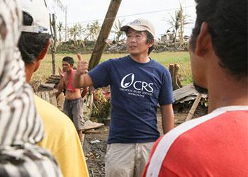 Un miembro del personal de CRS, Seki Hirano, Asesor técnico principal de refugios y reasentamientos (derecha) conversa con un carpintero, dos asistentes, y varios voluntarios que construyen un refugio de emergencia. Jim Stipe/CRS