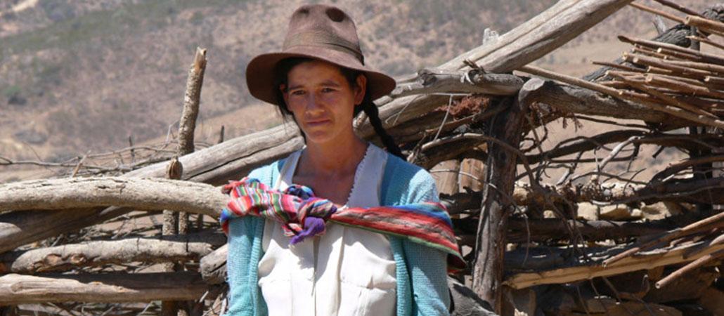 Rosalia Vargas posa frente a su pequeña casa en la que habitan ella, su esposo y cinco hijos. CRS trabaja con el socio ACLO (Fundación Loyola Cultural Action) para proveer tanques de agua en la árida población donde Rosalia vive.