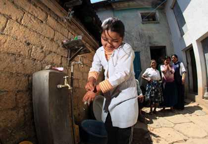 En las tierras bajas de Bolivia, donde el agua es abundante, Neisa Challco, de 8 años, se lava las manos debajo de un grifo que trae agua desde un sistema de agua construido con apoyo de un proyecto de CRS.