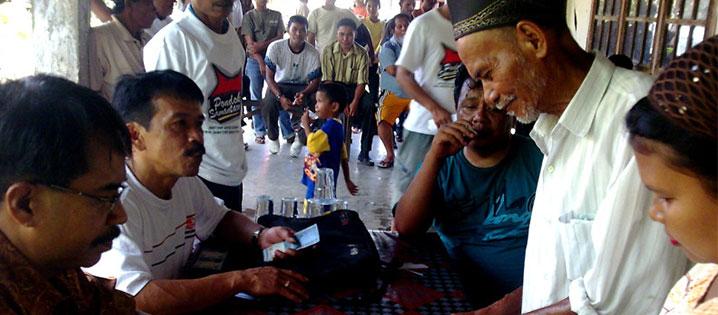 Beneficiarios indonesios recibieron subvenciones en efectivo para comprar materiales para construir pondoks (pequeñas casas de madera). Estos refugios transicionales proveen un espacio seguro después de un terremoto poderoso (el 30 de septiembre de 2009) que destruyó o dañó a muchas casas. Foto de Maria Josephine Wijiastuti/CRS