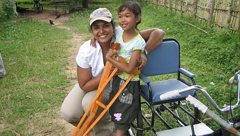Un miembro del personal de CRS con una joven beneficiaria del proyecto en la RDP Lao. CRS le otorgó una silla de ruedas y muletas para que pueda ir a la escuela y moverse alrededor de su comunidad. Foto de personal de CRS