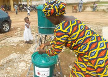 Una mujer en Guinea se lava las manos en un punto de lavado de manos público. CRS ha ofrecido capacitación y apoyo a voluntarios de la comunidad y líderes religiosos, visitas a los hogares, programas de radio, botiquines de higiene. Foto cortesía de Organisation Catholique pour la Promotion Humaine (Organización Católica para la Promoción Humana)