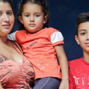 """Claudia, en la foto con su hija y su primo, vive en un pequeño pueblo de Honduras. Claudia intenta cultivar maíz y frijol en un pequeño solar fuera de la casa que comparte con su abuela, pero es demasiado seco y no hay mucha producción. """"Yo quiero más para mi hija. Yo quiero que ella vaya a la escuela y haga las cosas que yo nunca hice."""" Claudia trató de reunirse con su madre, que vive y trabaja en los Estados Unidos, pero el viaje era muy peligroso, y finalmente fue enviada de vuelta a Honduras."""