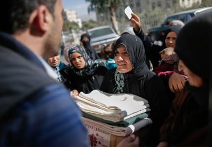 Una mujer siria reúne  cajas de ayuda y mantas en el Centro para Migrantes de Cáritas Líbano, que es apoyado por CRS, en Taalabaya, al este de Beirut.  Foto de Sam Tarling para CRS