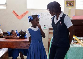 La maestra Maniela Dorcelus habla con una alumna en la escuela católica Notre Dame du Saint Esprit en el municipio de Hinche. Catholic Relief Services apoya programas educativos en Haití a través de la capacitación y certificación de los maestros de las escuelas locales. Foto de Oscar Leiva/Silverlight para CRS