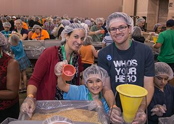 """La familia López, cubano-americana que participó en el programa """"Helping Hands"""" Manos Unidas empacando comida que será enviada al país de Burkina Faso."""