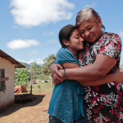 Portrait of Mayra Martinez, 11, and her grandmother Lucía Mancía, 62, outside their house at El Cedral, Jesús de Otoro, Intibucá, Honduras. Mayra was selected by her teacher to receive extra tutoring during the break between the 2013 and 2014 school years. The teacher noticed that she had learning difficulties, was unable to complete homework assignments, and missed class regularly. The Peer to Peer Tutoring Methodology offered by the USDA FFE project seemed like the perfect solution.  Her fellow classmate Elías Fabricio Hernandez and the local substitute seacher, both trained by the USDA FFE project staff, began working with Mayra with a specific focus on Spanish and Mathematics. Mayra successfully completed the Peer to Peer Tutoring program and was presented with a diploma by her tutor Elías. Her teacher is so proud of her stating that Mayra is no longer timid, does her homework, and comes to class on time. CRS implements the Food For Education Project with USDA in 17 municipalities in Intibucá, Honduras. The project benefits 53,863 children. CRS collaborates with Caritas Santa Rosa de Copan and COCEPRADII (El Comité Central Pro Agua y Desarrollo Integral de Intibucá). The two local organizations have years of experience in development and education projects in the south western part of Honduras.