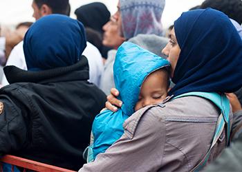Miles de refugiados del Norte de Africa y Medio Oriente han abandonado sus hogares por problemas económicos y amenazas de parte de grupos extremistas. Aquí decenas de refugiados se forman para recibir provisiones de parte de la Cruz Roja en Belgrado, Serbia. Foto de Kira Horvath para CRS.