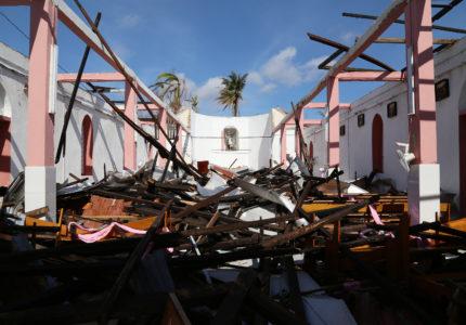Una estatua protegida en un nicho es todo lo que queda de pie en esta iglesia católica en la ciudad costera de Roche Bateau, Haití. La iglesia se encuentra entre miles de edificios y viviendas que fueron destruidas por un huracán de categoría cuatro el 4 de octubre. El huracán Matthew azotó los pueblos a lo largo de la península de Tiburón, en el suroeste de la costa de Haití, también conocida como el granero de Haití. Lluvias torrenciales y vientos de 233 kilómetros (145 millas) por hora derribaron árboles, arruinaron cosechas, arrastraron a personas y animales, y destruyeron hasta el 90 por ciento de los hogares en algunas zonas. Más de 2 millones de personas, aproximadamente la población de Houston, TX, se vieron afectadas, cientos de personas murieron y 1.4 millones de hombres, mujeres y niños necesitan ayuda de emergencia. No es sólo la costa que está padeciendo. La pérdida de cultivos pone en riesgo el bienestar de todo el país debido a que la zona es un productor clave del suministro de alimentos de Haití. El agua limpia es escasa y el saneamiento deficiente amenaza con desencadenar otro brote de cólera, una enfermedad que ha cobrado la vida de unas 10,000 personas desde el terremoto de 2010. Catholic Relief Services y socios locales de la Iglesia están jugando un papel fundamental para hacer frente a las necesidades de la comunidad y han estado en el sitio desde el primer día proporcionando suministros esenciales, como alimentos, mantas y otros suministros de emergencia. Para obtener más información, visita: crsespanol.org  Foto de Marie Arago for Catholic Relief Services