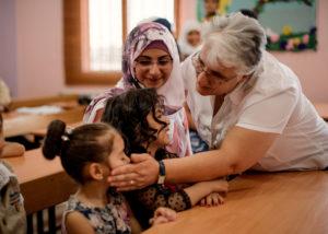 La hermana Amira Tabet abraza a un estudiante refugiado sirio en el Centro Comunitario de las Hermanas del Buen Pastor en Deir-al-Ahmar. CRS se asocia con las Hermanas del Buen Pastor para brindar oportunidades educativas a familias en situación de vulnerabilidad en 20 asentamientos informales en el área de Deir al Ahmar del Valle de Bekaa en el Líbano. CRS y las Hermanas del Buen Pastor brindan clases y apoyo con las tareas después de la escuela para niños sirios y libaneses. Los estudiantes aprenden materias tradicionales como matemáticas y ciencias, y participan en sesiones sobre construcción de paz. También pueden recibir educación sobre higiene, apoyo emocional y asesoramiento psicológico si es necesario. Lo que es más importante, el centro les ofrece a estos niños la oportunidad de volver a ser niños.